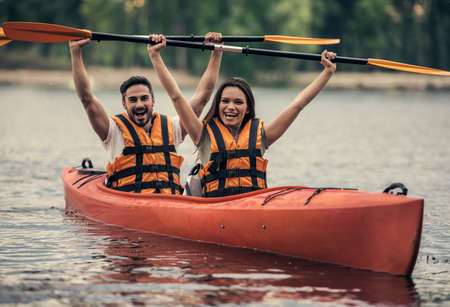 海ベストで幸せな若いカップルはカヤックを航行しながら笑っています。 写真素材 - 83936603