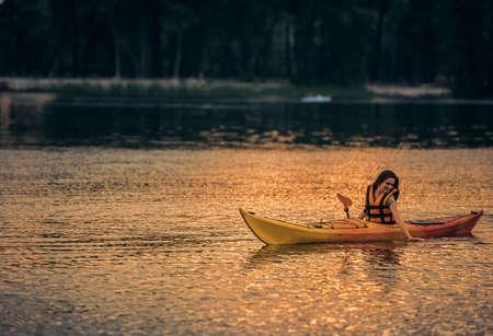 海のベストの美しい若い女性はカヤックを航行しながら笑っています。