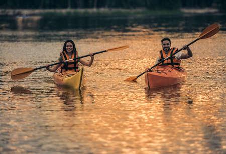 海ベストで幸せな若いカップルはカヤックを航行しながら笑っています。 写真素材 - 83936621