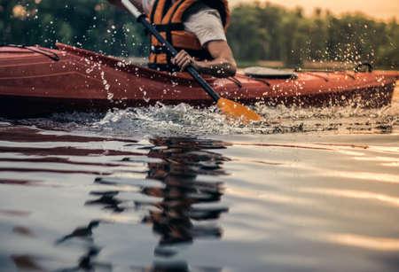Bebouwd beeld van de knappe jonge mens in overzees vest die een kajak varen Stockfoto - 83936624