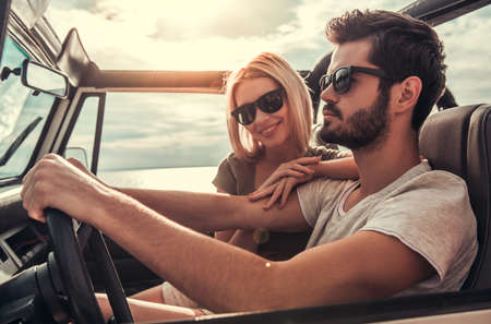 the jeep: Beautiful young couple is smiling while travelling by car in sunny weather