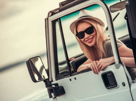 the jeep: Beautiful young couple is travelling by car, girl is looking at camera and smiling Stock Photo