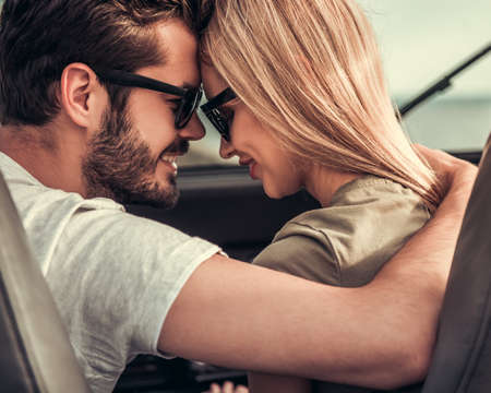 Het mooie jonge paar koestert en glimlacht terwijl het reizen door auto
