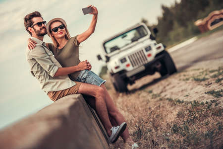 Beautiful couple is hugging and smiling while resting near the sea during their car trip, girl is doing selfie using a smart phone