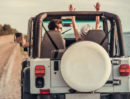 天候の良い日に車で旅行中楽しいを持っている美しい若いカップルの背面図 写真素材