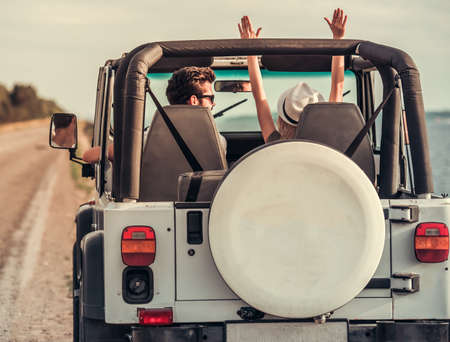 Back view of beautiful young couple having fun while travelling by car in sunny weather