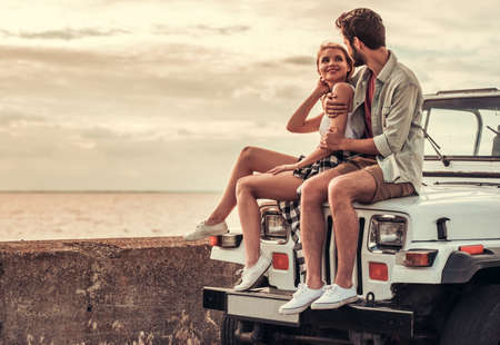 Beautiful couple is hugging and smiling while sitting on their car Stock Photo