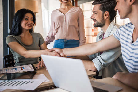 Beautiful young business people in casual clothes are communicating and smiling while working in office, man and woman are shaking hands