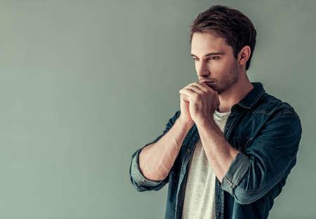 De knappe jonge mens in vrijetijdskleding houdt handen samen zoals het bidden, op grijze achtergrond