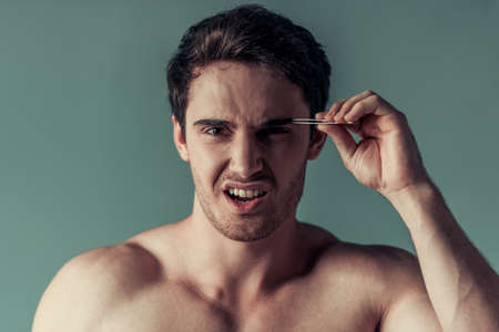 Portrait of handsome young man with bare shoulders grimacing while plucking the eyebrows, on gray background