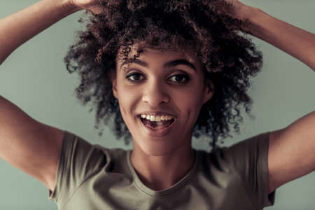 Portrait of beautiful Afro American girl playing with her curly dark hair, looking at camera and smiling, on gray background