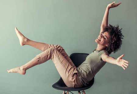 カジュアルな服で美しいアフロ アメリカン ガールは椅子に座って、楽しんで、灰色の背景に