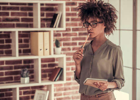 Beautiful Afro American business woman in smart casual wear and eyeglasses is thinking while standing with a notepad in office Stok Fotoğraf