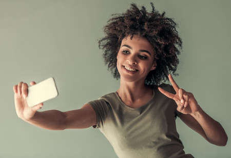 Beautiful Afro American girl is doing selfie using a smart phone and smiling, on gray background Stock Photo
