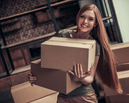 Beautiful young woman is holding cardboard boxes, looking at camera and smiling while moving into new apartment