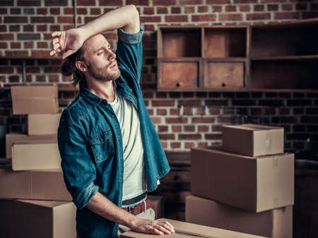 Handsome guy is moving into new apartment; wiping his forehead while arranging cardboard boxes