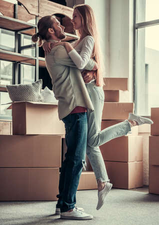 Full length portrait of beautiful young couple hugging among cardboard boxes and smiling while moving into new apartment