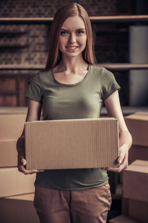 Beautiful young woman is holding a cardboard box, looking at camera and smiling while moving into new apartment