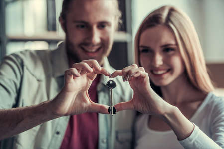 Beautiful young couple is holding a key, making a heart and smiling while moving into new apartment