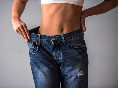 Cropped image of beautiful Afro American girl in large size jeans showing her weight loss, on gray background