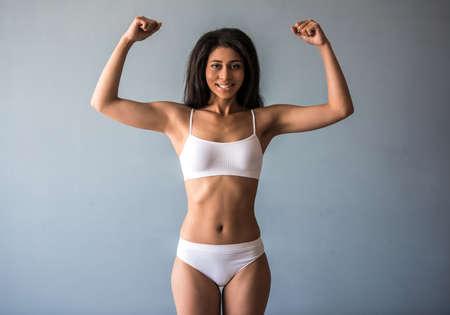 아름 다운 아프리카 계 미국인 스포츠 소녀 카메라를보고 웃 고, 회색 배경에 그녀의 근육을 보이고있다