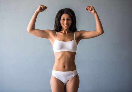 Beautiful Afro American sports girl is showing her muscles, looking at camera and smiling, on gray background Stock Photo