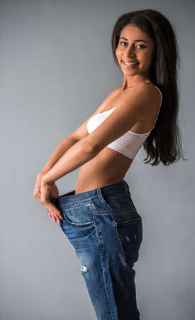 Beautiful Afro American girl in large size jeans is showing her weight loss and smiling, on gray background Stock Photo