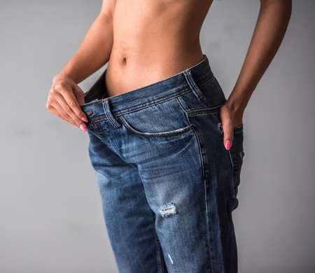 body dimensions: Cropped image of beautiful Afro American girl in large size jeans showing her weight loss, on gray background