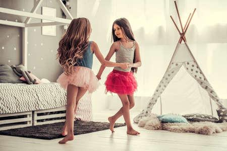Zwei glückliche kleine Mädchen tanzen und lächeln beim im Kinderzimmer zu Hause spielen Standard-Bild - 84680756