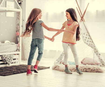 Two happy little girls are dancing and smiling while playing in children's room at home