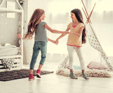 Twee gelukkige meisjes dansen en glimlachen terwijl ze thuis spelen in de kinderkamer