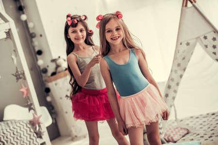 Twee gelukkige meisjes in kronen doen elkaar haar, bekijken camera en glimlachen terwijl thuis het spelen in de ruimte van kinderen