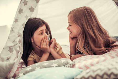 二人のかわいい少女が話していると、子供のテントで一緒にプレーしながら笑みを浮かべて