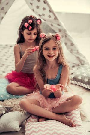 Twee gelukkige meisjes in kronen doen elkaar haar en glimlachen terwijl ze thuis spelen in de kinderkamer Stockfoto
