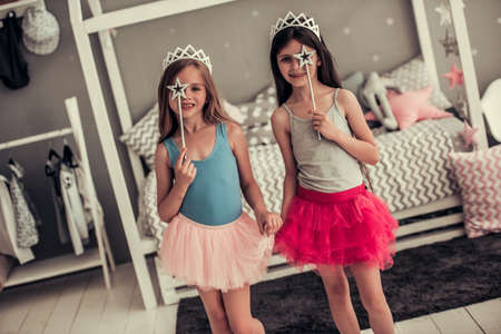 冠で幸せな二人の少女が魔法の杖を保持している、カメラ目線、子供部屋、自宅で再生しながら笑みを浮かべて
