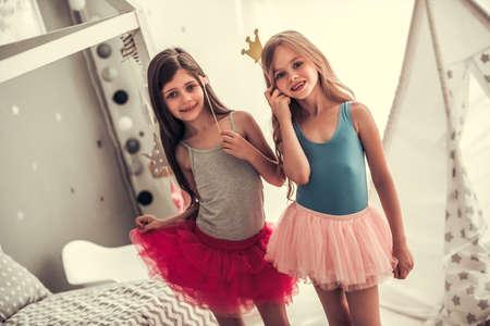 Twee gelukkige kleine meisjes in kronen houden partijsteunen, bekijken camera en glimlachen terwijl thuis het spelen in de ruimte van kinderen Stockfoto