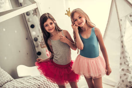 Two happy little girls in crowns are holding party props, looking at camera and smiling while playing in childrens room at home