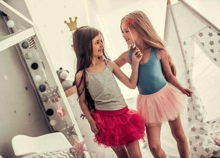 Twee gelukkige kleine meisjes in kronen houden partijsteunen, bekijken elkaar en glimlachen terwijl thuis het spelen in kinderkamer