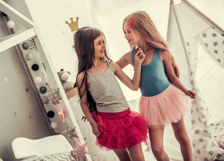 Two happy little girls in crowns are holding party props, looking at each other and smiling while playing in childrens room at home