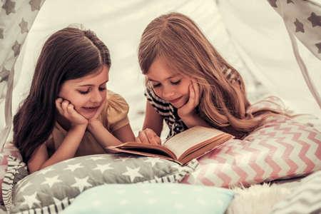 Deux petites filles mignonnes lisent un livre et souriant tout en jouant ensemble dans le tipi de l'enfant