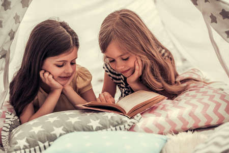 Two cute little girls are reading a book and smiling while playing together in child's teepee