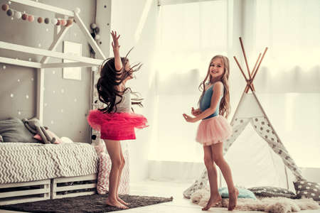 Two happy little girls are dancing and smiling while playing in childrens room at home