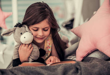 Cute little girl is reading a book, hugging her toy and smiling while lying on bed in her room at home