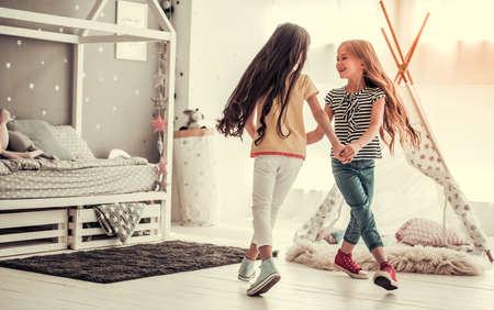 Zwei glückliche kleine Mädchen tanzen und lächeln beim Spielen im Kinderzimmer zu Hause Standard-Bild - 84850497