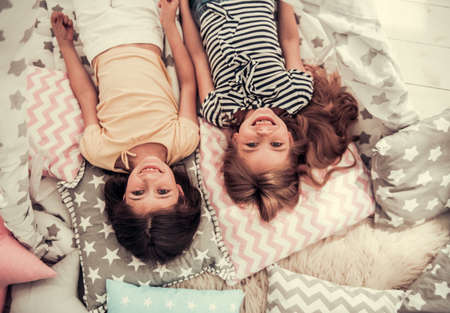Top view of two cute little girls looking at camera and smiling while playing together at home
