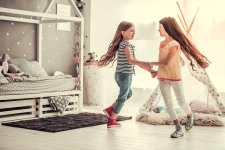 Zwei glückliche kleine Mädchen tanzen und lächeln beim Spielen im Kinderzimmer zu Hause Standard-Bild - 84851924