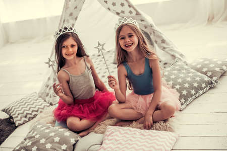 Two happy little girls in crowns are holding magic wands, looking at camera and smiling while playing in children's room at home
