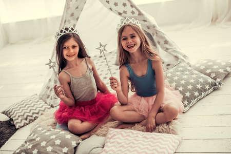Due bambine felici in corone stanno tenendo le bacchette magiche, guardando la fotocamera e sorridendo mentre giocano nella stanza dei bambini a casa