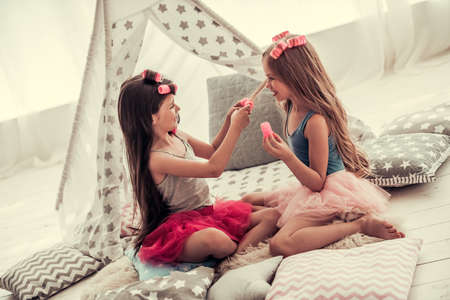 Two happy little girls in crowns are doing each other hair and smiling while playing in childrens room at home