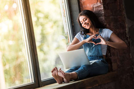 Beautiful Afro American girl in denim overall is using a laptop, showing a heart and smiling while sitting on the window sill at home